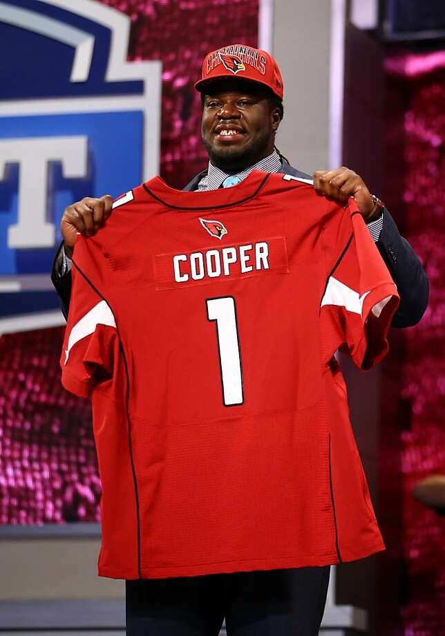 NEW YORK, NY - APRIL 25:  Jonathan Cooper of North Carolina Tar Heels holds up a jersey on stage after he was picked #7 overall by the Arizona Cardinals in the first round of the 2013 NFL Draft at Radio City Music Hall on April 25, 2013 in New York City.  (Photo by Al Bello/Getty Images) Photo: Al Bello, Getty Images