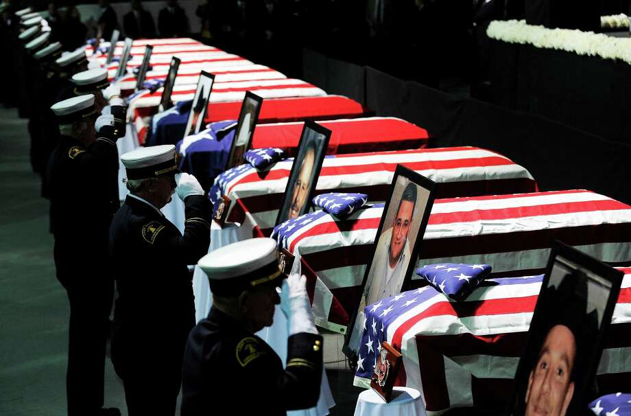 Firefighters salute in front of caskets and photos of their colleagues at Wednesday's memorial service at Baylor University for the firefighters who perished last week. Photo: JEWEL SAMAD, Staff / AFP