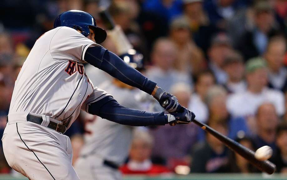 Jason Castro of the Astros makes contact on a hit against the Red Sox.