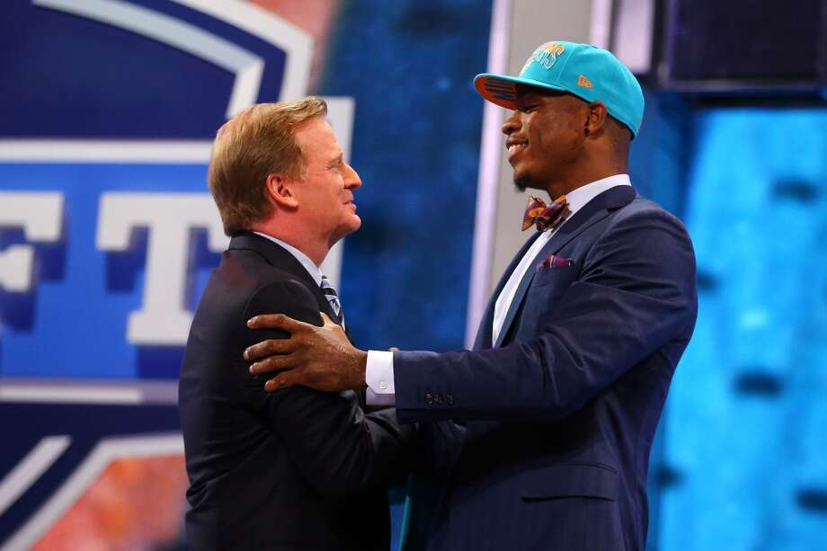 Dion Jordan (R) of the Oregon Ducks greets NFL Commissioner Roger Goodell after Jordan was picked #3 overall by the Miami Dolphins in the first round of the 2013 NFL Draft at Radio City Music Hall on April 25, 2013 in New York City.