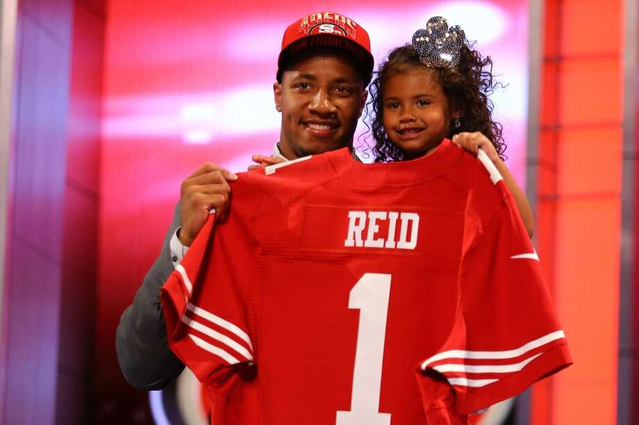 Eric Reid of the LSU Tigers holds his daughter as they hold up a jersey on stage after he was picked #18 overall by the San Francisco 49ers.