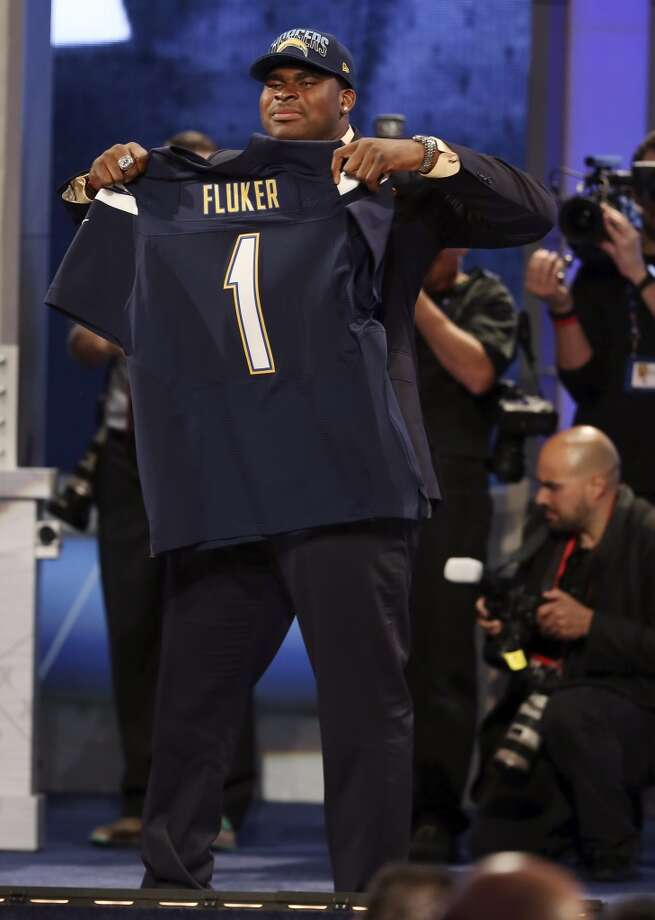 D.J. Fluker, from Alabama, holds up a team jersey after being selected 11th overall by the San Diego Chargers in the first round of the NFL football draft, Tuesday, April 23, 2013, at Radio City Music Hall in New York.