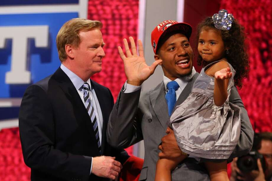 Eric Reid of the LSU Tigers holds his daughter Leilani as they stand with NFL Commissioner Roger Goodell as they hold up a jersey on stage after Reid was picked #18 overall by the San Francisco 49ers in the first round of the 2013 NFL Draft at Radio City Music Hall on April 25, 2013 in New York City.