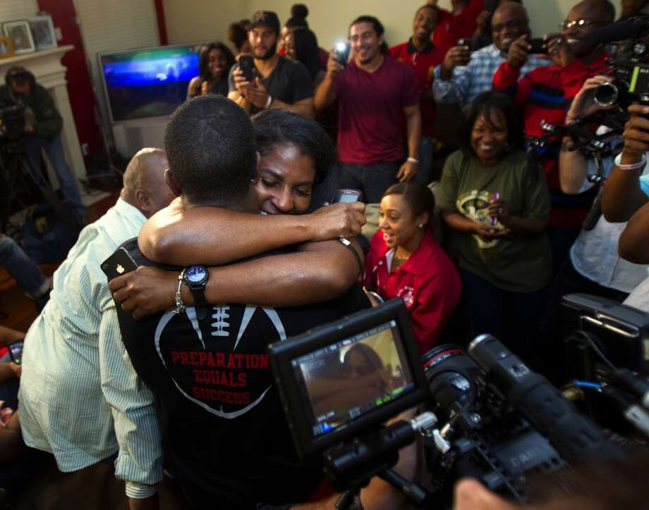 D.J. Hayden from Houston, left, hugs his mother Tori Hayden after he was selected 12th overall by the Oakland Raiders in the NFL football draft at his house in Missouri City, Texas.