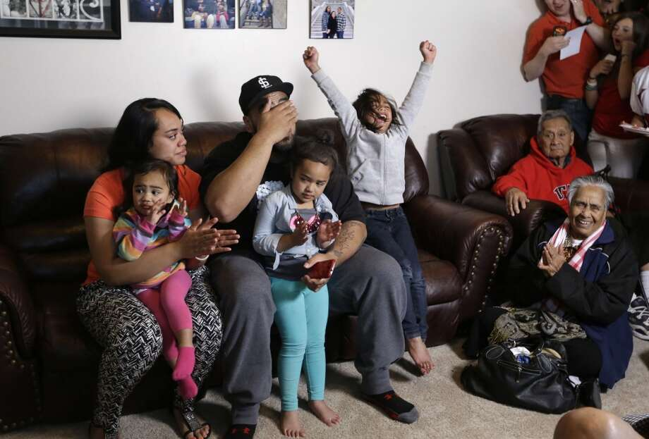 Star Lotulelei, from Utah, reacts next to his wife Fuiva as they hold their daughters Pesatina, 1, left, and Arilani, 3, center, while his niece Elyena Tukuafu, 5, right, cheers after he was selected 14th overall by the Carolina Panthers during an NFL football draft party at their home, Thursday, April 25, 2013, in South Jordan, Utah. (AP Photo/Rick Bowmer)