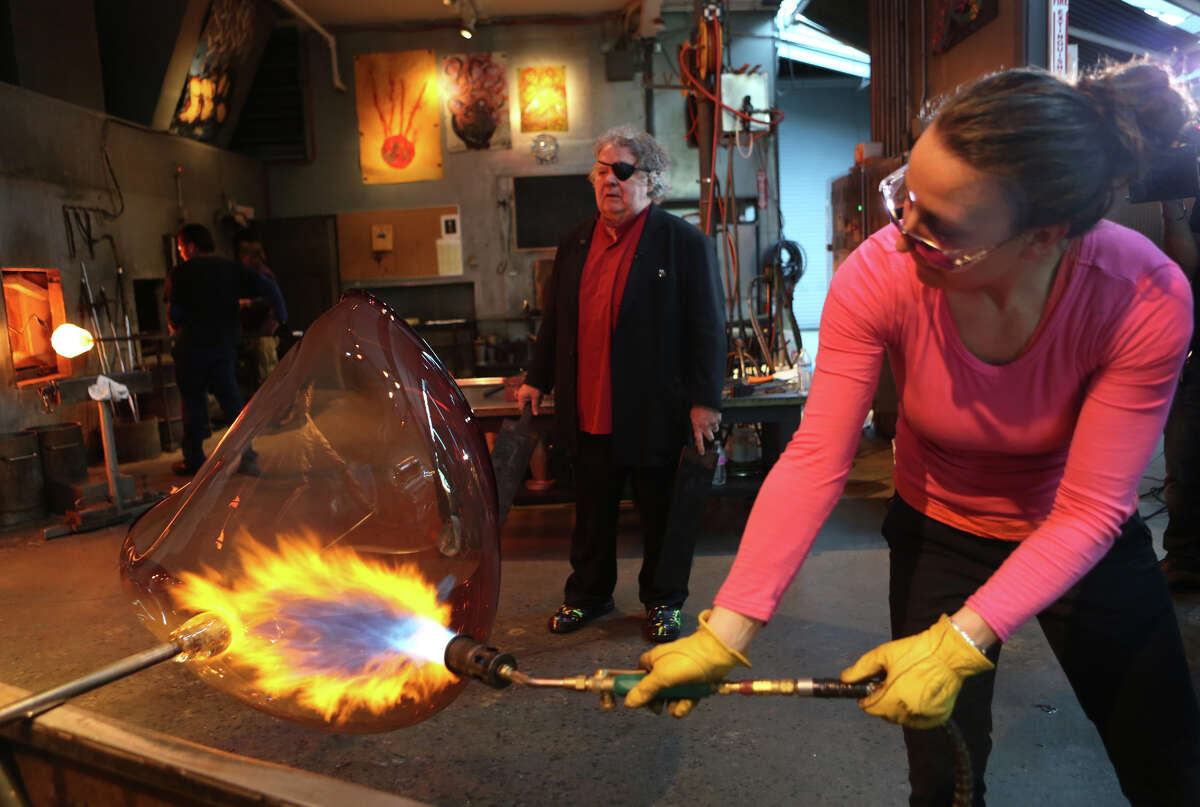 Rosalie Battah applies fire as Dale Chihuly waits to shape the glass as his team of glass artists work on one in a series of