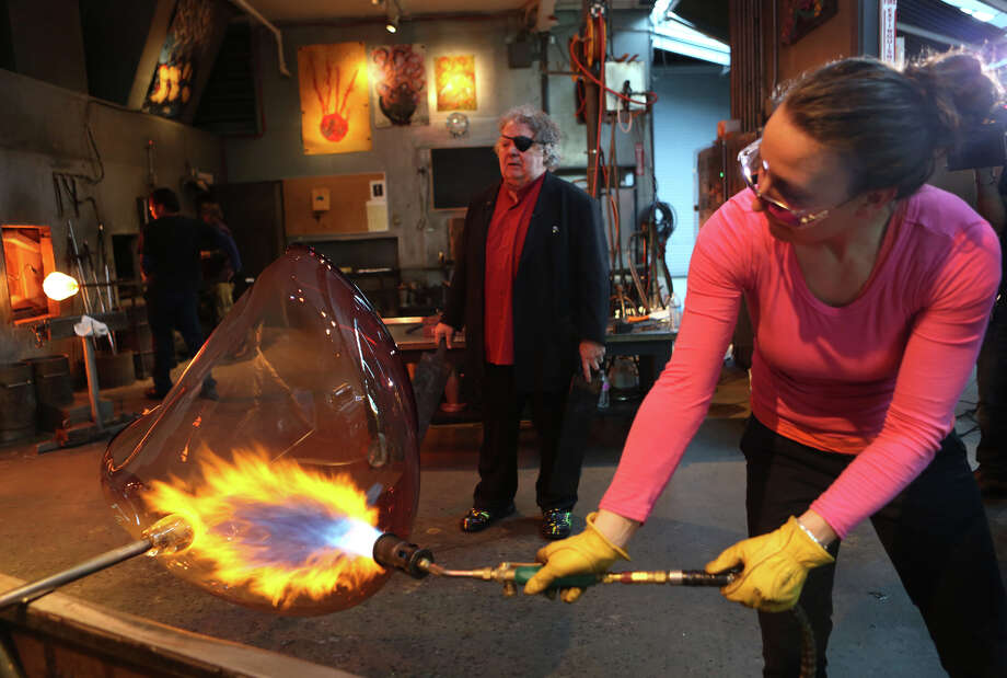 "Rosalie Battah applies fire as Dale Chihuly waits to shape the glass as  his team of glass artists work on one in a series of ""fire orange baskets"" at the artist's Lake Union Boathouse on Thursday, April 25, 2013. The orange hue baskets, among the largest he has created, will be part of a temporary installation in the Glasshouse at the Chihuly Garden and Glass. Read more about the installation here. Photo: JOSHUA TRUJILLO, SEATTLEPI.COM / SEATTLEPI.COM"
