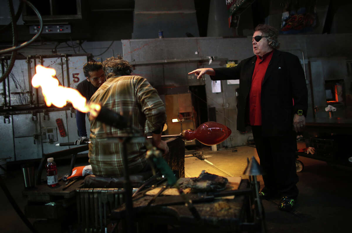 Artist Dale Chihuly watches over his team of glass artists as they work on one in a series of