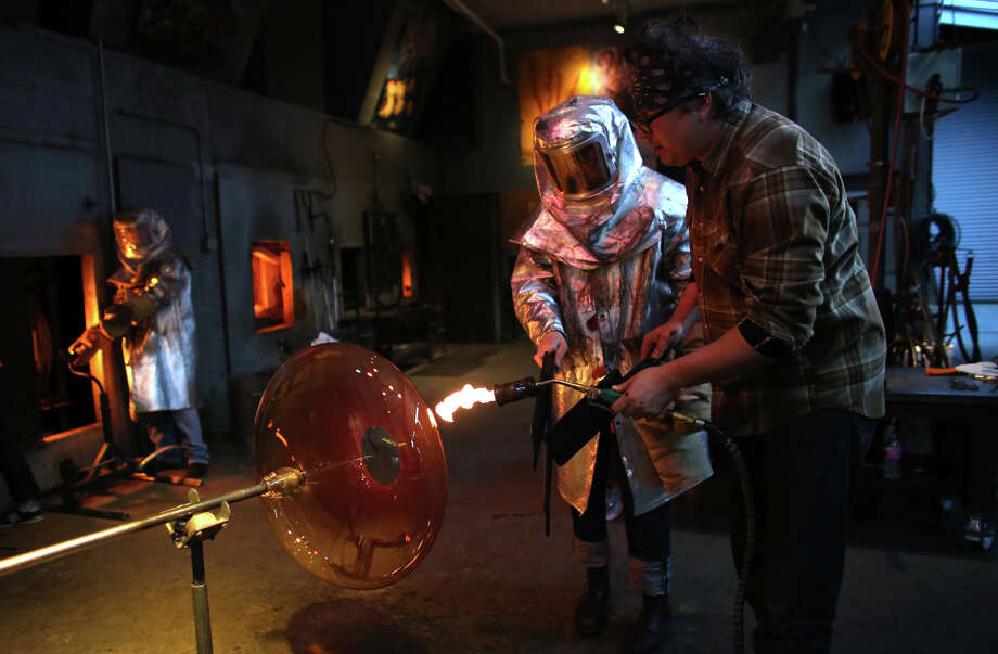 Lead gaffer Jim Mongrain, right, heats glass in Dale Chihuly's Lake Union Boathouse. The glass will become one of his fire orange baskets, among the largest he has created. They will be part of a temporary installation in the Glasshouse at the Chihuly Garden and Glass. Photo: JOSHUA TRUJILLO, SEATTLEPI.COM / SEATTLEPI.COM