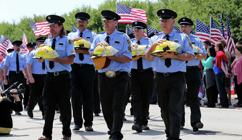 Helmets of the fallen firefighters are carried into the services as firefighters congregate at Baylor University in Waco on Thursday. Photo: TOM REEL