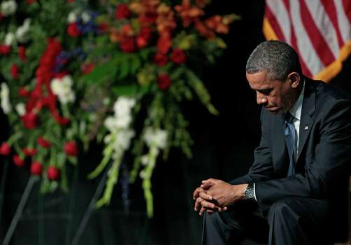 President Obama bows his head. Photo: Erich Schlegel, Getty Images / 2013 Getty Images