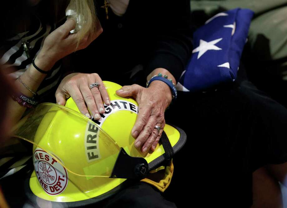 A family member holds a flag and helmet. (AP Photo/Eric Gay) Photo: Eric Gay, Associated Press / AP