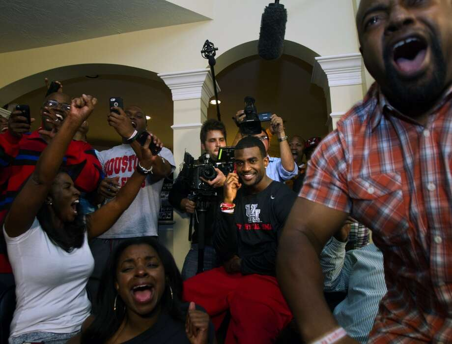 D.J. Hayden from Houston, center, smiles as he receives a call from the Oakland Raiders telling him he was selected 12th overall in the NFL football draft at his house in Missouri City, Texas.