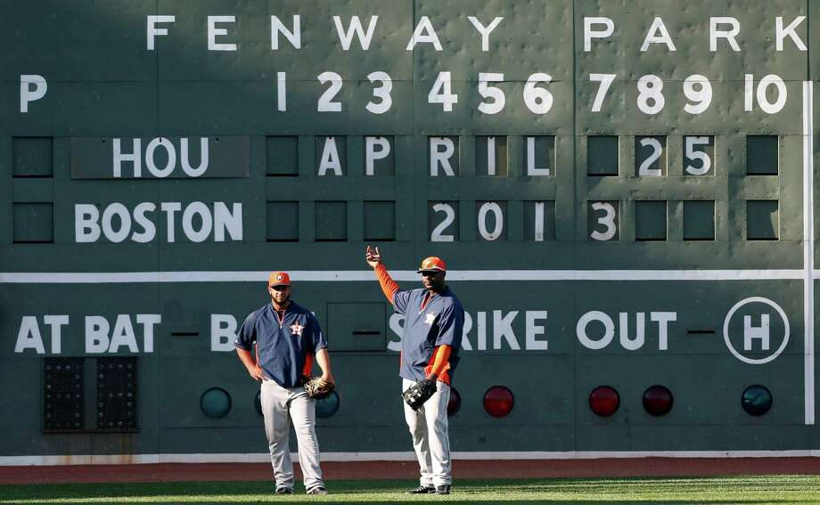 Astros outfielders Fernando Martinez and Chris Carter prepare to take pregame flies in front of the Green Monster at Fenway Park, the majors' oldest ballpark. Photo: Michael Dwyer, STF / AP