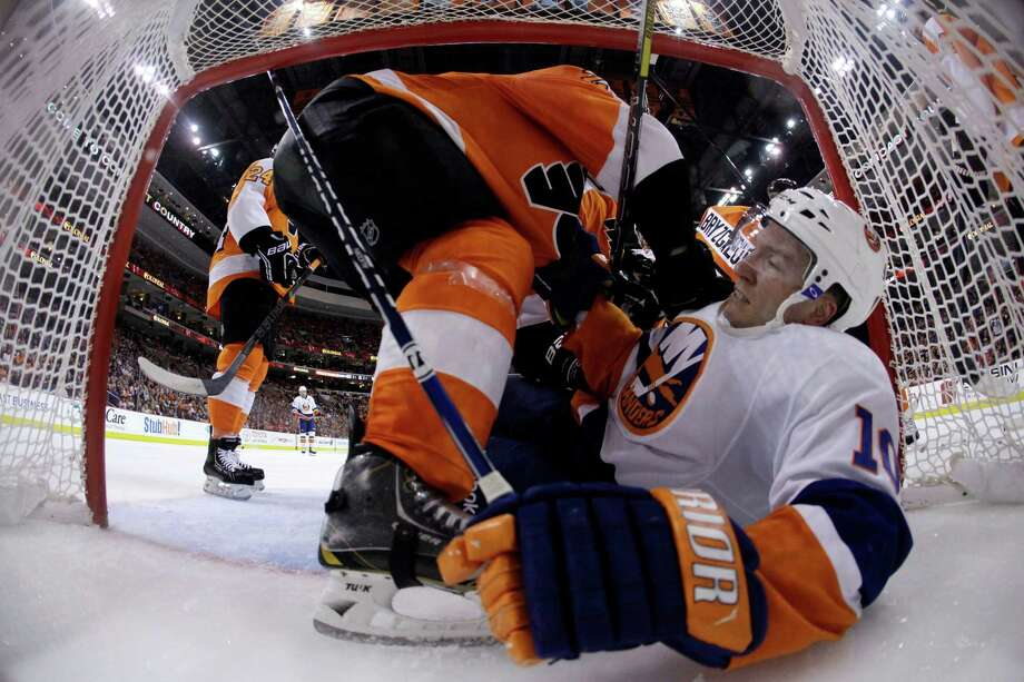 New York Islanders' Keith Aucoin, right, is knocked to the ice by Philadelphia Flyers' Luke Schenn after Aucoin crashed into the net during the third period of an NHL hockey game, Thursday, April 25, 2013, in Philadelphia. Philadelphia won 2-1. (AP Photo/Matt Slocum) Photo: Matt Slocum