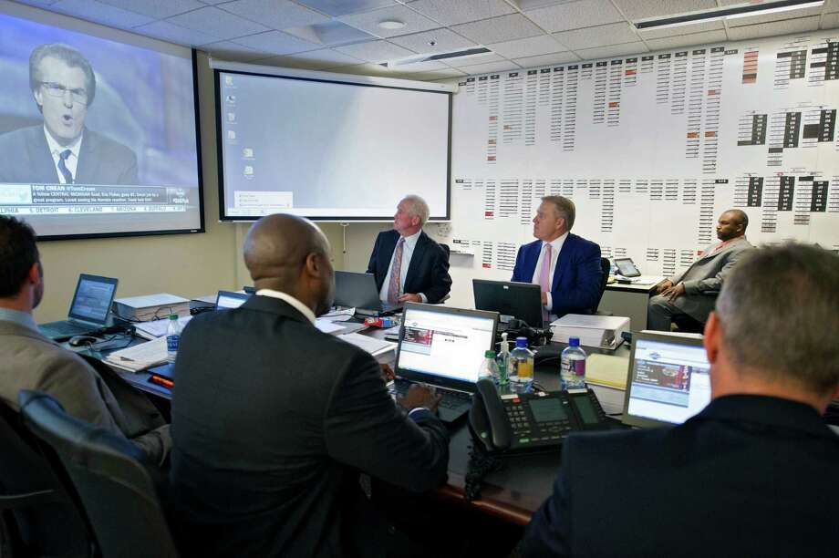 "This photo provided by the Denver Broncos shows head coach John Fox, back left, and vice president John Elway, center facing camera, in the ""War Room"" at the NFL football team's headquarters in Englewood, Colo., on Thursday, April 25, 2013. The Broncos are scheduled to pick 28th in the first round. (AP Photo/Denver Broncos, Eric Bakke) Photo: Eric Bakke"