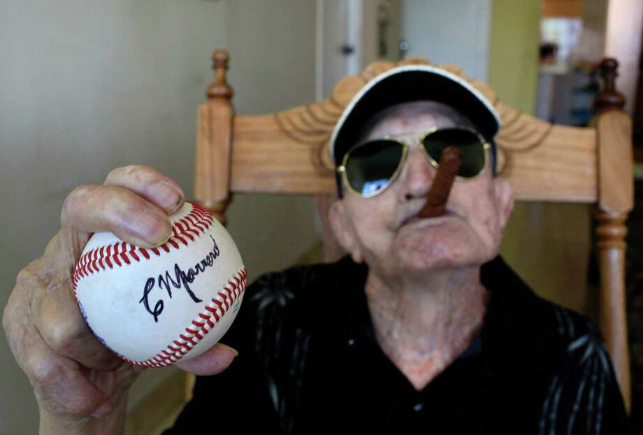 In this April 23, 2013 photo, Cuba's former pitcher Conrado Marrero, the world's oldest living former major league baseball player, holds up a baseball with his signature at his home, two days before is 102nd birthday, as he holds an unlit cigar in his mouth in Havana, Cuba. In addition to his longevity, the former Washington Senator has much to celebrate this year. After a long wait, he finally received a $20,000 payout from Major League baseball granted to old-timers who played between 1947 and 1979. The money had been held up since 2011 due to issues surrounding the 51-year-old U.S. embargo on Cuba, which prohibits most bank transfers to the Communist-run island. But the payout finally arrived in two parts, one at the end of last year, and the second a few months ago, according to Marrero's family. (AP Photo/Franklin Reyes) Photo: Franklin Reyes