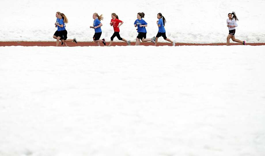 Snow covers all but a ribbon of track as seventh graders from Central, Gruening and Hanshew Middle Schools compete at 800 meters in a track meet at Begich Middle School in Anchorage, Alaska.  Photo: Erik Hill, Associated Press