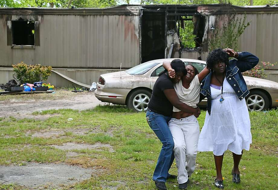 Leigh Hawkins, center, weeps for her four grandchildren who were killed in a fire at their mobile home the day before in Hartsville, S.C., Thursday, April 25, 2013.  Authorities say smoke inhalation killed 10-month-old twin sisters Myasia and Kynasia Hawkins and their brothers, 2-year-old Camaron Mason and 4-year-old Delonta Dixon. Hawkins daughter is the children's mother. Photo: Gavin Jackson, Associated Press