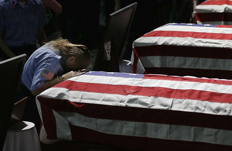 West EMT Terase Alexander leans on the casket of West firefighter Cyrus Reed following a memorial service for victims of the fertilizer plant explosion in West, Texas, Thursday, April 25, 2013, in Waco, Texas.  Photo: Eric Gay, Associated Press