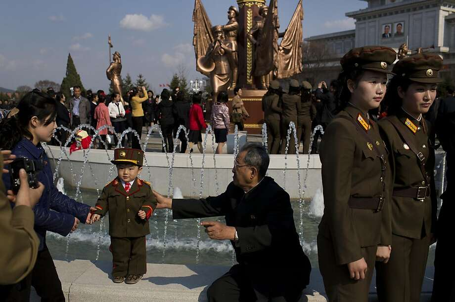 North Korean soldiers and civilians pose for souvenir photos in front of a fountain as they tour the grounds of Kumsusan Palace of the Sun, the mausoleum where the bodies of the late leaders Kim Il Sung and Kim Jong Il lie embalmed, in Pyongyang on Thursday, April 25, 2013. North Korea on Thursday marked the 81st anniversary of the founding of its military, which began as an anti-Japanese militia and now has an estimated 1.2-million troops.  Photo: David Guttenfelder, Associated Press