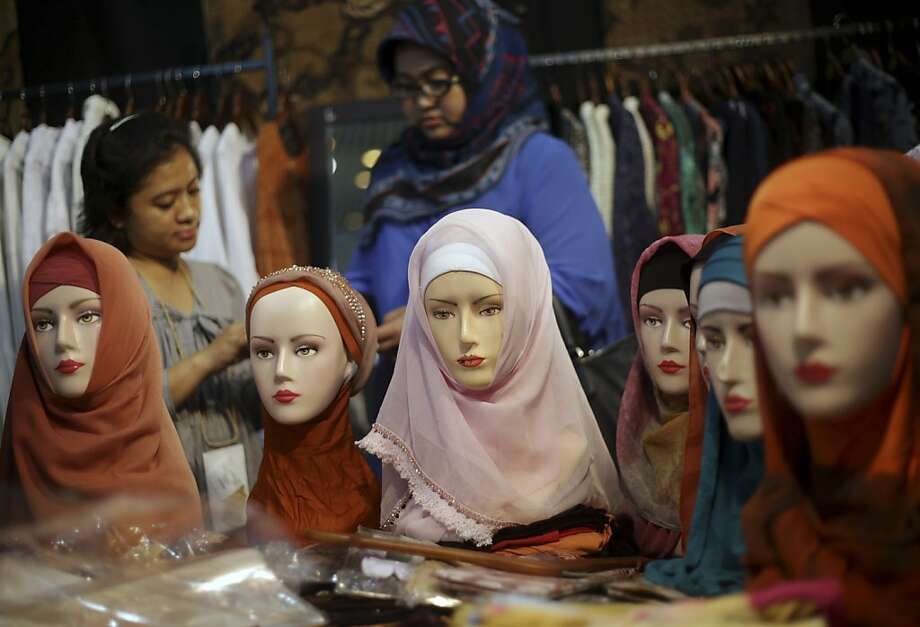 Indonesian women shop for Muslim headscarves at a craft exhibition in Jakarta, Indonesia, Thursday, April 25, 2013.  Photo: Dita Alangkara, Associated Press