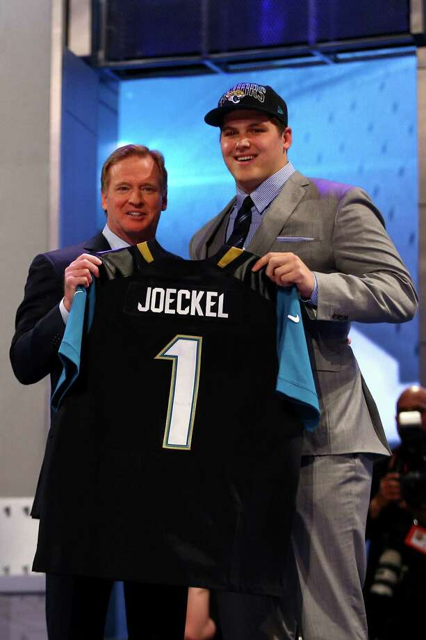 Texas A&M's Luke Joeckel holds up a Jacksonville Jaguars jersey as he meets commissioner Roger Goodell on Thursday after being the fifth Aggie selected second overall in the NFL draft. Photo: Al Bello / Getty Images