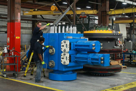 Ken Rickley, left, and Jacolbe Phillips assembling a double ram blowout preventer at National Oilwell Varco. Ken is a BOP assembly lead man, and Jacolbe is a BOP assembler.