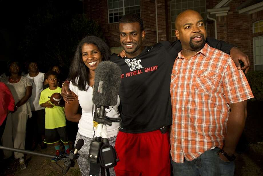D.J. Hayden, center, stands with his mom, Tori Hayden, left, and father, Derek Hayden, right, after he was picked by the Oakland Raiders.