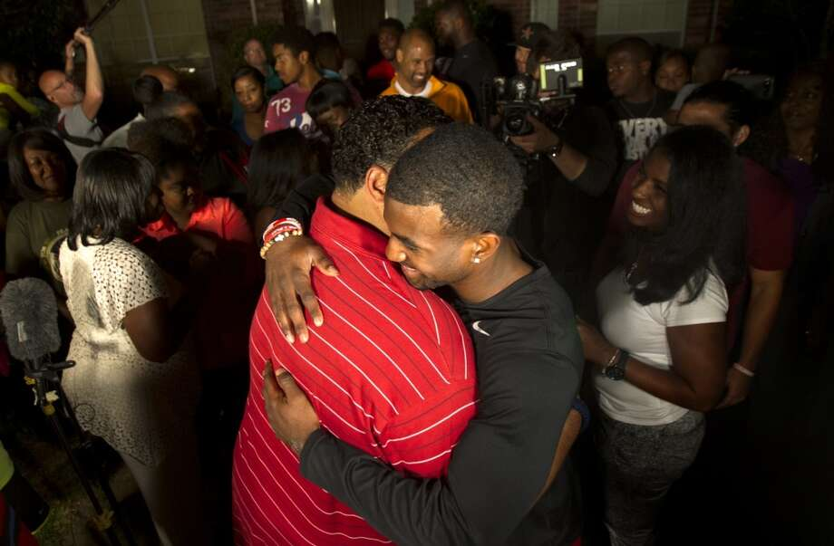 D.J. Hayden, right, receives a hug from UH team chaplain Mikado Hinson.