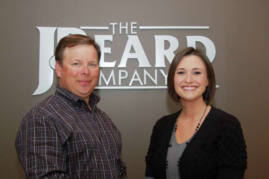 Jeff Beard, left, president of the J. Beard Real Estate Co., welcomes Lindsey McKean of The Woodlands as a new broker agent.