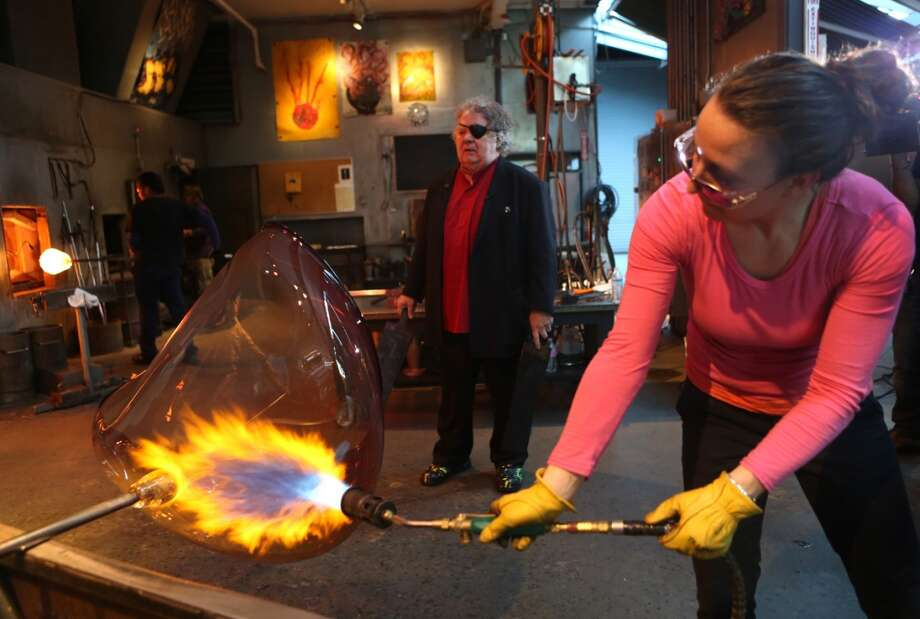 "Rosalie Battah applies fire as Dale Chihuly waits to shape the glass as  his team of glass artists work on one in a series of ""fire orange baskets"" at the artist's Lake Union Boathouse on Thursday, April 25, 2013. The baskets, among the largest he has created, will be part of a temporary installation in the Glasshouse at the Chihuly Garden and Glass. (Joshua Trujillo, seattlepi.com)"