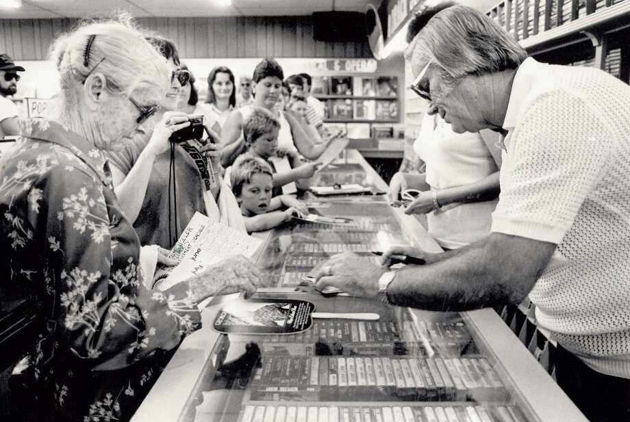 George Jones signs an autograph for Etta Runnels of Vidor at The Record Rack while other fans wait for their turn. Jones was in Beaumont to sign autographs and greet fans. Photo: The Beaumont Enterprise archives.