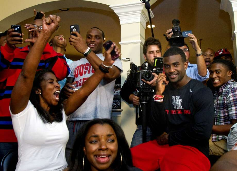 Tori Hayden, left, reacts as her son D.J. Hayden from Houston, right, receives a phone call from the Oakland Raiders telling him he was selected 12th overall in the NFL football draft at his house in Missouri City, Texas.