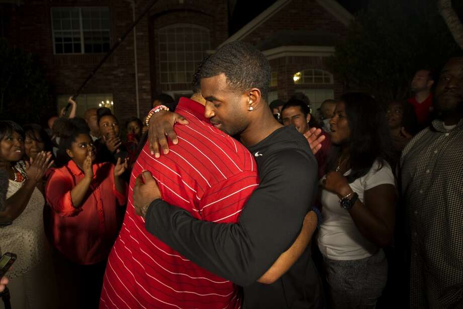 Former University of Houston player D.J. Hayden, right, receives a hug from U of H team chaplain Mikado Hinson, left, after he was picked by the Oakland Raiders in the 2013 NFL draft at his house Thursday, April 25, 2013, in Missouri City.