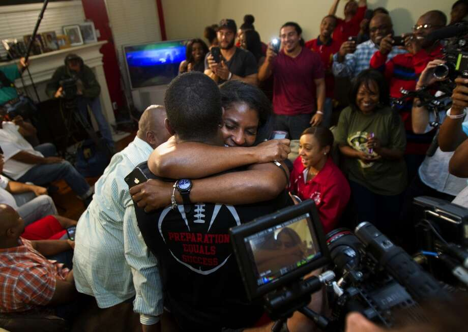 Former University of Houston player D.J. Hayden, left, hugs his mom, Tori Hayden, after he was picked by the Oakland Raiders in the 2013 NFL draft at his house Thursday, April 25, 2013, in Missouri City.