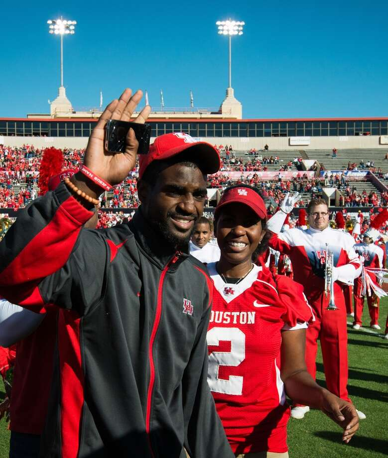 Houston cornerback D.J. Hayden waves to the crowd after being recognized before a college football game against Tulane at Robertson Stadium, Saturday, Nov. 24, 2012, in Houston. Hayden had surgery to repair a tear in the main blood vessel that leads to the heart, an injury suffered when he collided with a teammate during practice earlier in the month.  Behind Hayedn is his mother, Tori Hayden.