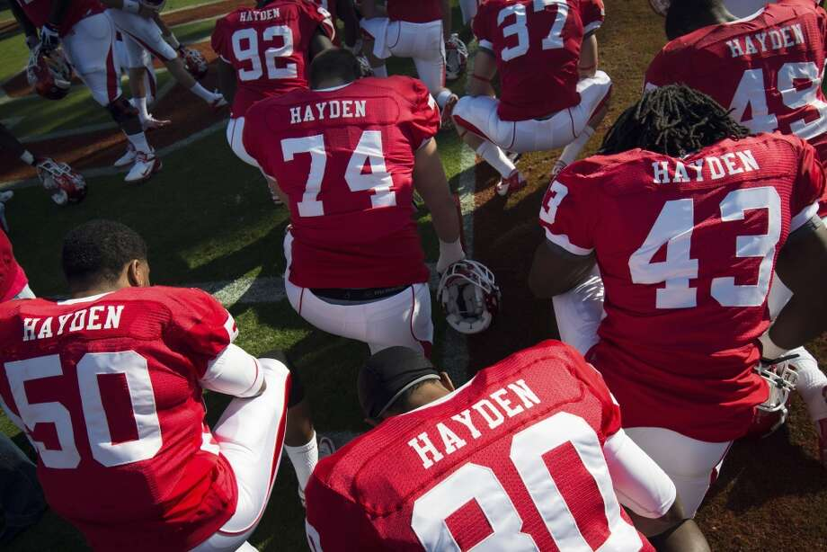 In this Nov. 24, 2012, photo, Houston players wear jerseys that all bear the name of cornerback D.J. Hayden as they kneel in prayer before a college football game against Tulane in Houston. Hayden had surgery to repair a tear in the main blood vessel that leads to the heart, an injury suffered when he collided with a teammate during practice.