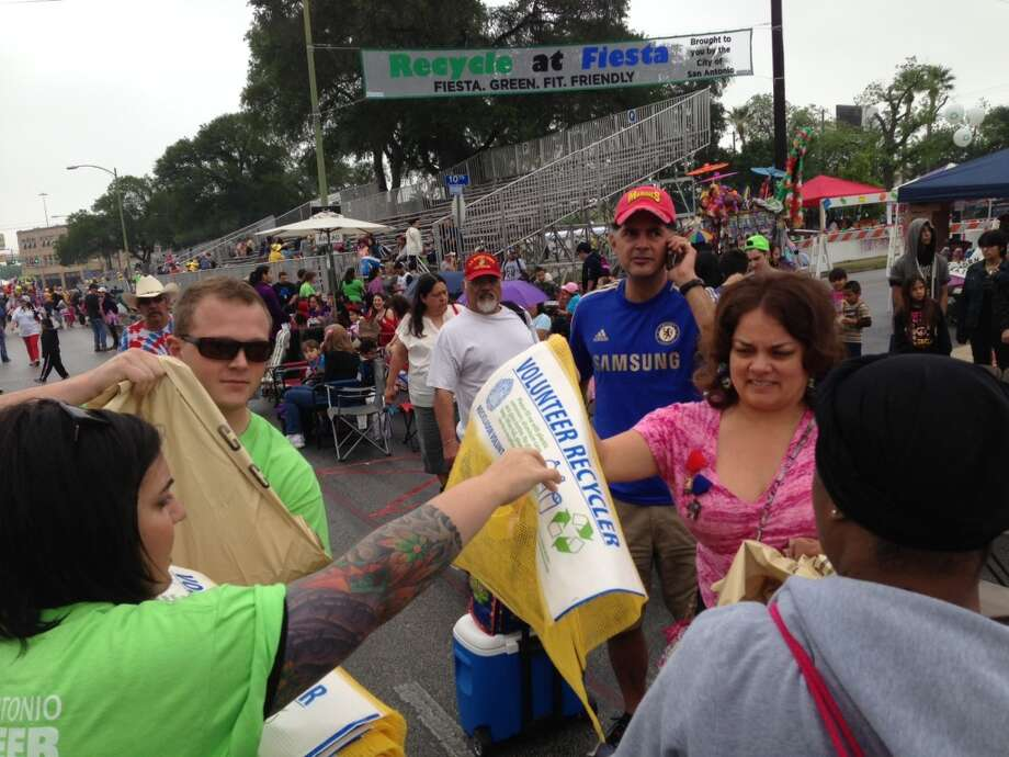 Volunteers distribute trash and recycle bags.