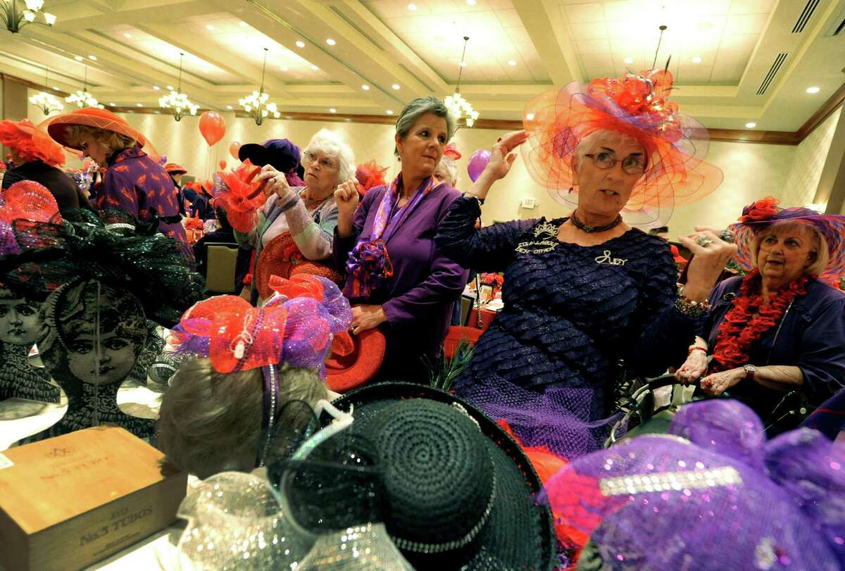 Judy Pinto of East Greenbush tries on a hat designed by Betty Parker during a national Red Hat Society day gathering at the Hilton Garden Inn in Clifton Park during on Thursday April 25, 2013 in Clifton Park, N.Y. (Michael P. Farrell/Times Union)