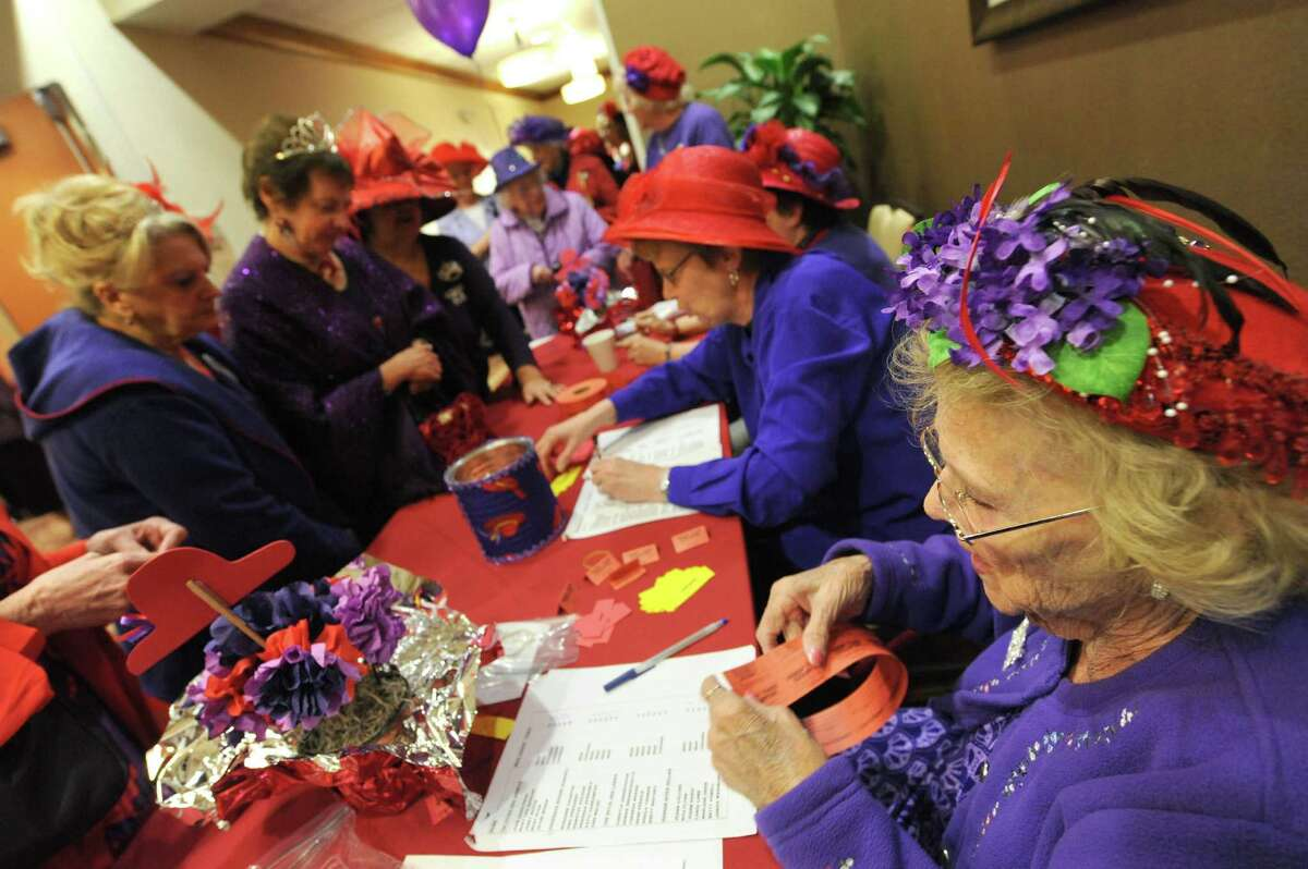 Dorothea Garneau of Troy, right, takes care of raffle tickets at check in during a national Red Hat Society day gathering at the Hilton Garden Inn in Clifton Park during on Thursday April 25, 2013 in Clifton Park, N.Y. The Spindle City Divas sponsored the event. (Michael P. Farrell/Times Union)