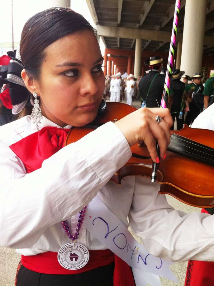 Fox Tech senior Jennifer Garcia, 18, practicing with fellow SAISD mariachi students at the start of the Battle of Flowers Parade route. Photo: Jennifer Lloyd / Express-News