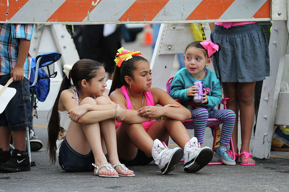 Young spectators (from left) Jerrilyn Mann, Melanie Gaitan and Natalia Rubio watch the vanguard from under a barricade on Alamo Street as the Battle of Flowers Parade moves through the downtown area  on  April 26 2013. Photo: TOM REEL, Tom Reel / Express-News