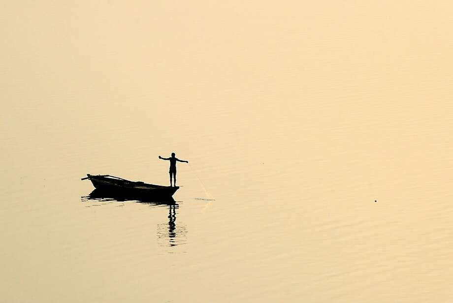 A fisherman pulls in his netfrom a skiff on the Yamuna River in Allahabad, India. Photo: Sanjay Kanojia, AFP/Getty Images
