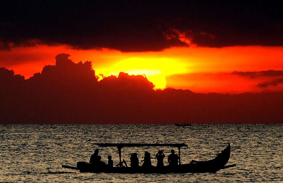 Bali beauty:Foreigners take a sunset boat tour off Bali's Kuta beach. Photo: Sonny Tumbelaka, AFP/Getty Images