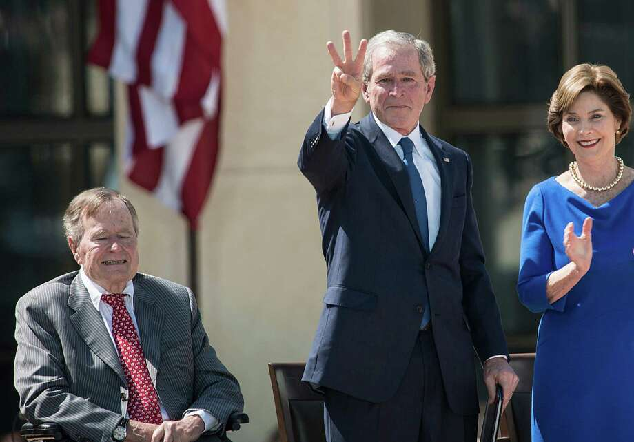 """Former President George W. Bush makes a """"W"""" with his fingers at the dedication ceremony for the George W. Bush Library and Museum. Bush's record looks better as time passes. Photo: Brendan Smialowski / AFP / Getty Images"""