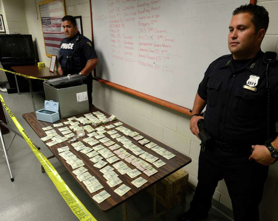 Troy Police officers Evangelista Negron, left and Michael Harrington stand guard on approximately $115,000 in cash at Police Headquarters  that was confiscated during the course of a drug raid at 2534 5th Avenue in Troy, N.Y. Sept. 14, 2012.     Arrested was Jamaine Myers at the 5th Avenue address.   (Skip Dickstein/Times Union) Photo: Skip Dickstein