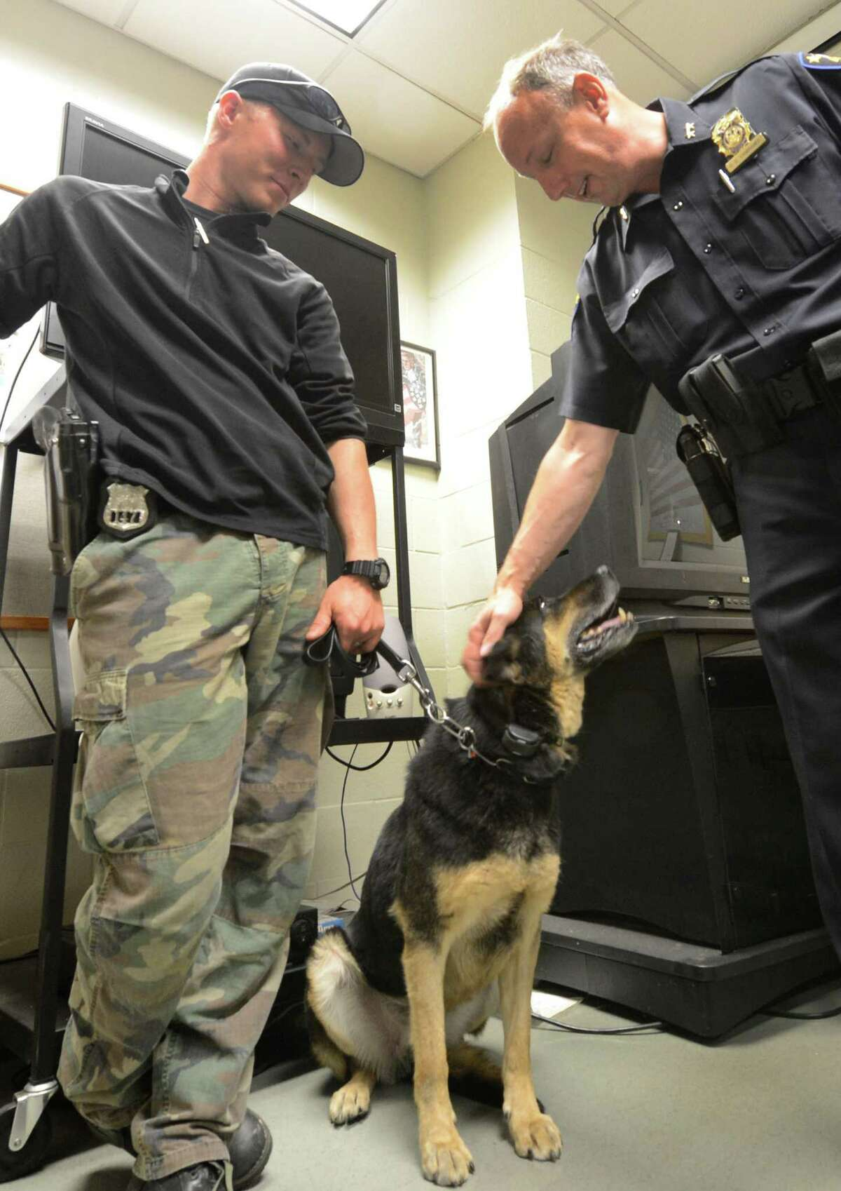 Troy Police Officer Justin Ashe, left is joined by Assistant Chief Geroge VanBramer as he gives K-9 officer Elza after drug raid which the K-9 alerted on a stash of cocaine which lead to the confiscation of approximately $115,000 in cash during a drug raid at 2534 5th Avenue in Troy, N.Y. Sept. 14, 2012. Arrested was Jamaine Myers at the 5th Avenue address. (Skip Dickstein/Times Union)