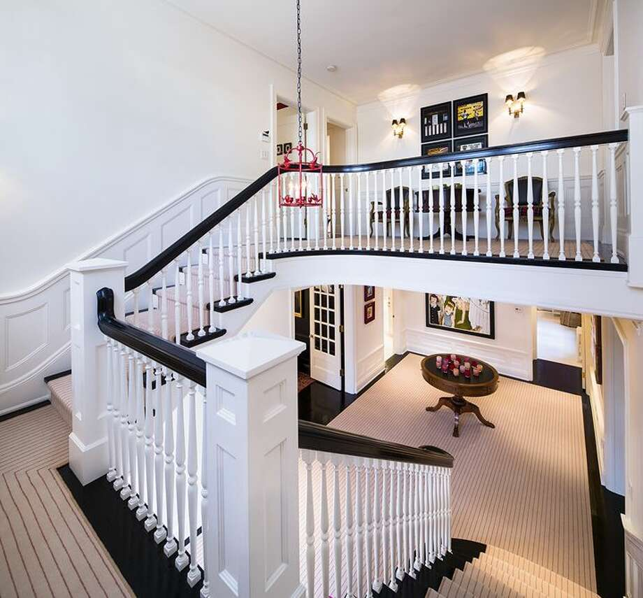 Stairway of 1658 Federal Ave. E. The 7,380-square-foot Colonial-style mansion, built in 1919, has five bedrooms, five bathrooms, a two-story entry hall, a family room, a sun room, an office, a sitting room and a home theater on a nearly half-acre lot with two terraces, a play structure, a sports court, a storage shed with stone-clad walls and a built-in dog house, and a detached two-car garage topped by a dog run. It's listed for $4.25 million. Photo: Courtesy Mary Snyder And Bob Bennion, Windermere Real Estate