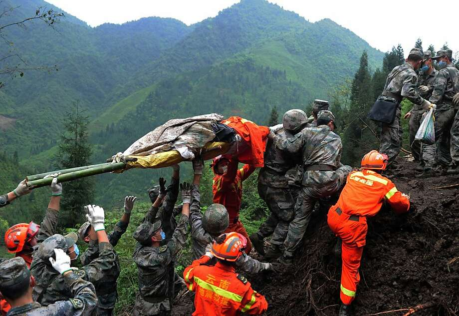 Rescuers carry the body of an earthquake victim in Lushan county of Yaan, China. Tens of thousands of survivors remain homeless after last Saturday's devastating temblor. Many lack food and supplies. Photo: Afp, AFP/Getty Images